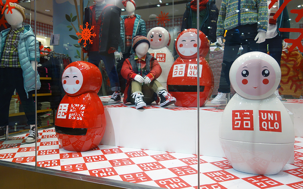 Christmas window display with red and white large dolls